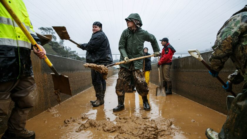OROVILLE, CALIF. -- FRIDAY, FEBRUARY 17, 2017: Volunteers help shovel the muddy sediment that has bu