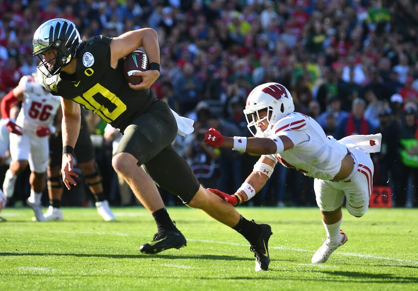 Oregon quarterback Justin Herbert breaks loose from Wisconsin safety Reggie Pearson to score a touchdown during the first quarter of the Rose Bowl.