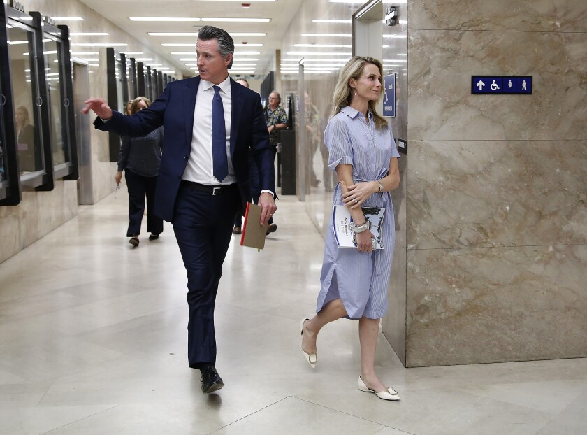 """FILE - In this May 9, 2019, file photo, California Gov. Gavin Newsom and his wife, First Partner Jennifer Siebel Newsom, return to the Governor's Office after a news conference in Sacramento, Calif. California Gov. Gavin Newsom said he """"absolutely"""" sees no conflict of interest with a nonprofit launched by his wife accepting donations from companies that lobby his administration. (AP Photo/Rich Pedroncelli, File)"""