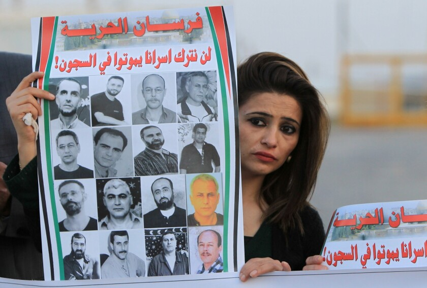 A Palestinian woman holds a poster Saturday bearing pictures of Arab detainees being held in Israeli prisons since before the 1993 Oslo peace accords. Palestinians were protesting the postponement of the release of the prisoners outside the gates of Ofer prison, near the West Bank town of Betunia.