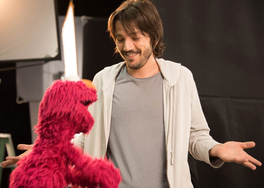 """Actor Diego Luna appears with muppet character Elmo on the new Spanish-language series """"Sesame Amigos,"""" debuting Aug. 1 on Univision."""