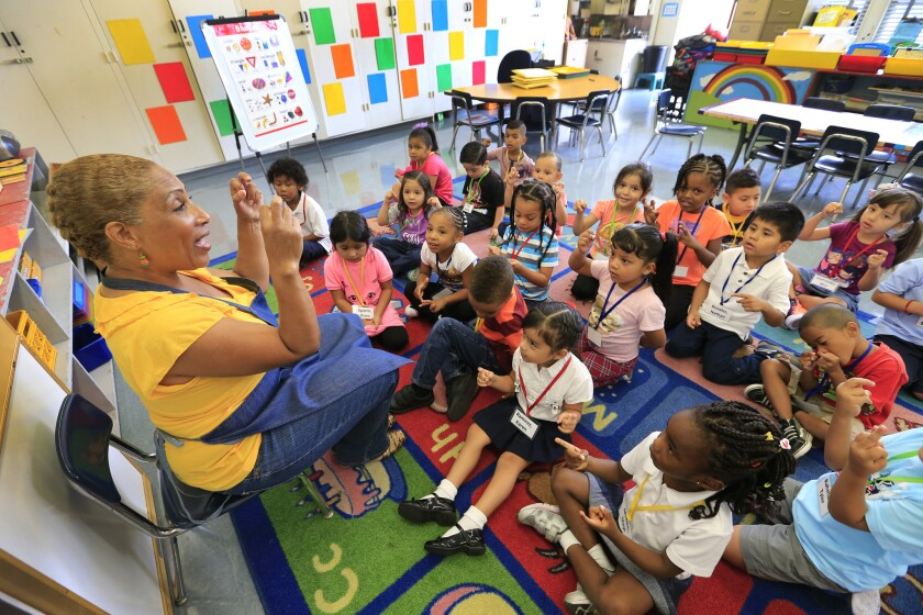 Children in L.A. Unified School District's expanded transitional kindergarten program join in a song with teacher Lisa Harmison during their first day of school at 186th Street Elementary in Gardena.