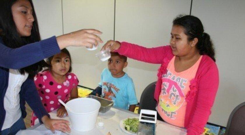 Students in Casa de Amistad's summer program make zucchini bread. The Solana Beach program is now seeking volunteers for the school year. Photo/Karen Billing