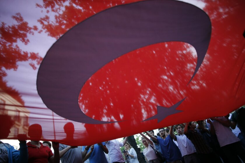 Turkish protesters connected with Turkey's opposition Nationalist Movement Party (MHP), hold a big Turkish flag, during a rally outside the German consulate in Istanbul, Thursday, June 2, 2016. The protesters rallied against the decision made by the German parliament earlier Thursday that overwhelm