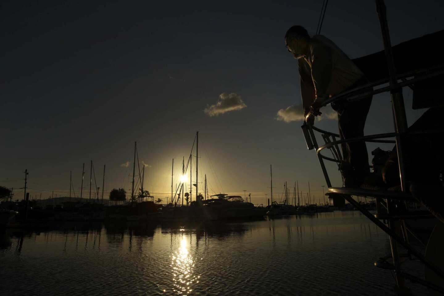 Live-aboard boat owner John Loftus watches the setting sun from the deck of his 43-foot sailboat moored at the Colonial Yacht Anchorage in Wilmington. He is among 95 boat owners who were served with eviction notices last month.