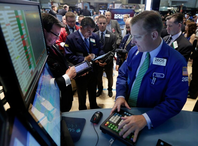 Specialist Edward Zelles, foreground, works with traders at his post on the floor of the New York Stock Exchange Monday, June 2, 2014. Stocks were moving slightly lower in early trading Monday following the release of a closely watched report that showed an unexpected slowdown in U.S. manufacturing last month. The market is coming off record highs last week. (AP Photo/Richard Drew)