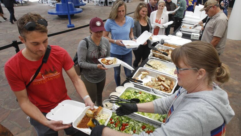 Kelly Shaw serves corn to Ryan Mesmer, a hydrologic technician for the U.S. Geological Survey, during the Free Lunch for 500 Federal Workers event, put on by Yelp San Diego, San Diego Aerospace Museum, and various restaurants, in Balboa Park.