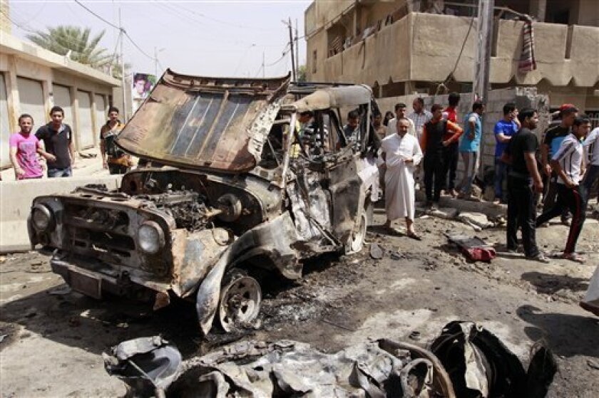 Civilians gather at the scene of a car bomb attack in the east Baghdad neighborhood of Kamaliya, Iraq, Monday, April 15, 2013. A series of attacks across, Iraq many involving car bombs, has killed and wounded dozens of people, police said less than a week before Iraqis in much of the country are sc