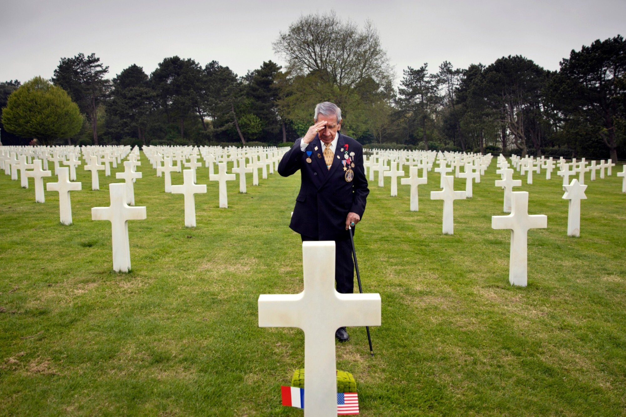 World War II and D-day veteran Charles Norman Shay from Indian Island, Me., salutes the grave of fellow soldier Edward Morozewicz at the Normandy American Cemetery in Colleville-sur-Mer in France in 2019.