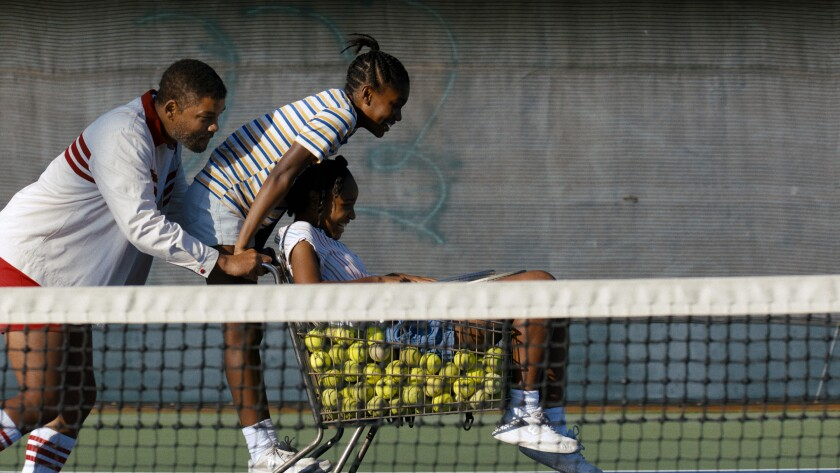 Will Smith pushes two girls on a grocery cart full of tennis balls.