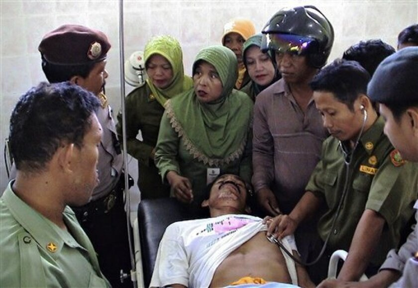 Relatives of a victim of the 700-ton Teratai Prima, a ferry which sank in heavy weather, gather around him who was rescued from the water Monday, Jan. 12, 2009 at a hospital in Majene, west Sulawesi, Indonesia. Rocky seas hindered rescuers Monday as they searched for nearly 250 people missing and f