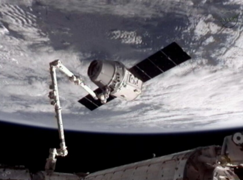 This image provided by NASA-TV shows the SpaceX Dragon commercial cargo craft, top, after Dragon was grappled by the Canadarm2 robotic arm and connected to the International Space Station in May 2012. A similar procedure, scheduled for Wednesday, could be pushed back because a robotics system backup part needs repair.
