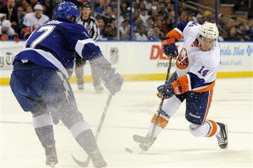 New York Islanders defenseman Thomas Hickey, right, shoots against Tampa Bay Lightning center Alex Killorn during the first period of an NHL hockey game, Thursday, March 14, 2013, in Tampa, Fla. (AP Photo/Brian Blanco)