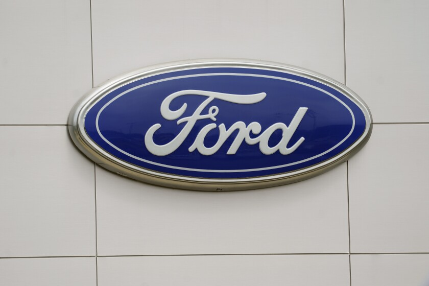 A Ford logo is seen on signage at Country Ford in Graham, N.C., Tuesday, July 27, 2021. Ford Motor Co. has hired a former executive from Apple and Tesla to be the company's head of advanced technology and new embedded systems, a critical post as the auto industry moves to adopt vehicles powered by electricity and guided by computers. (AP Photo/Gerry Broome)