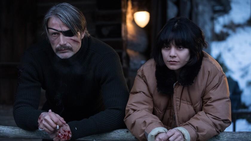 "Mads Mikkelsen and Vanessa Hudgens in the movie ""Polar."""