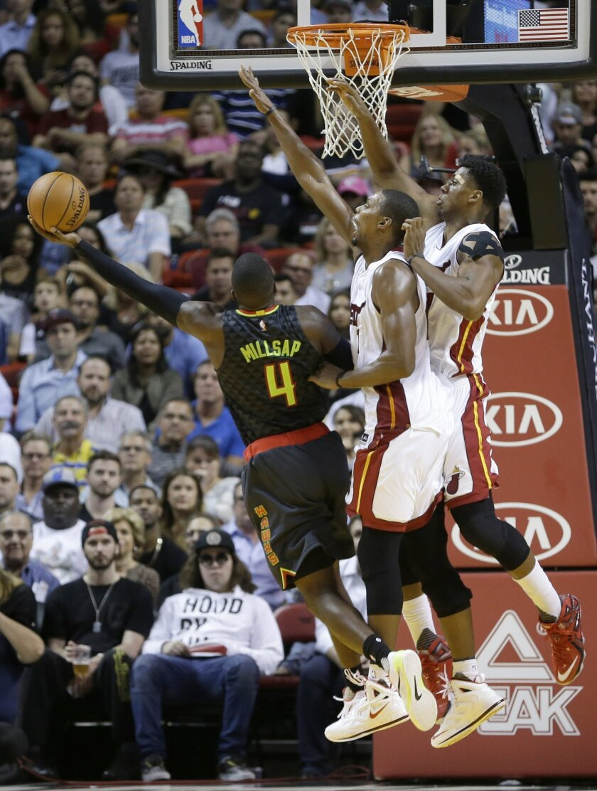 Atlanta Hawks forward Paul Millsap (4) goes to the basket against Miami Heat forward Chris Bosh, center, and Hassan Whiteside, right, during the first half of an NBA basketball game, Tuesday, Nov. 3, 2015, in Miami. (AP Photo/Alan Diaz)