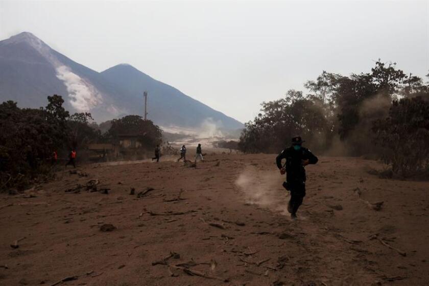 Un policía corre por un deslizamiento de fluido del volcán de Fuego hoy, lunes 4 de junio de 2018, después de la erupción, en el Caserío San Miguel Los Lotes, Escuintla (Guatemala). EFE