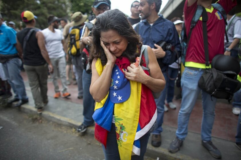 An anti-government protester holds a Venezuelan flag as security forces block the opposition from reaching the National Electoral Council in Caracas.