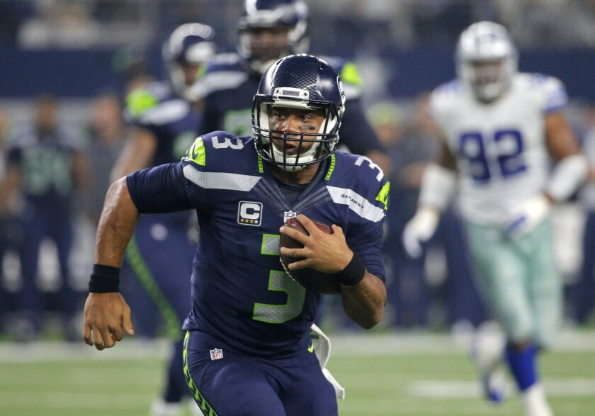 Seattle Seahawks' Russell Wilson (3) runs the ball late in the second half of an NFL football game against the Dallas Cowboys, Sunday, Nov. 1, 2015, in Arlington, Texas. (AP Photo/Brandon Wade)