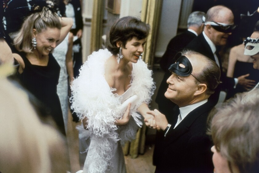 Truman Capote greets elegantly dressed party guests.