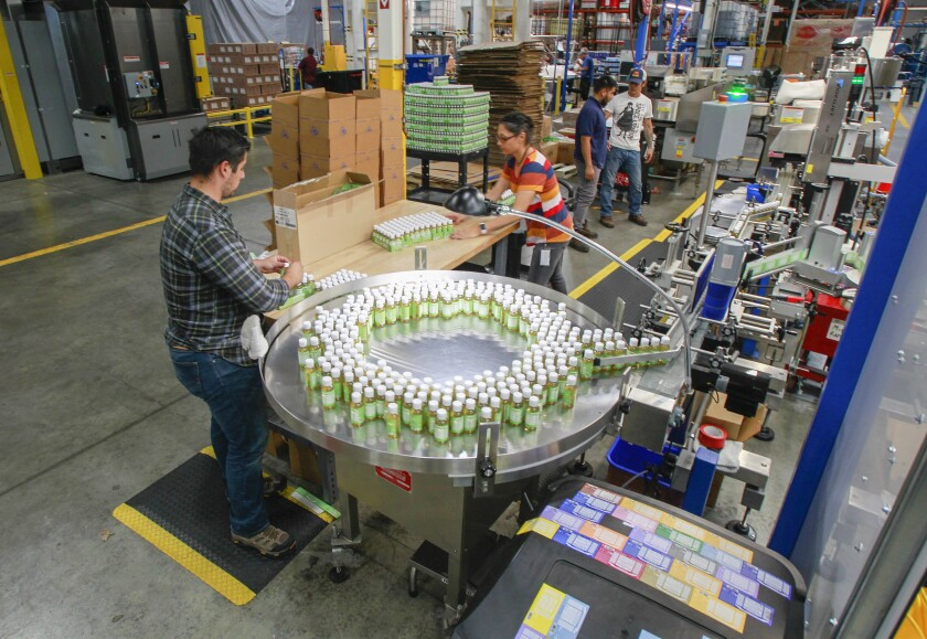 Employees work in the packaging area at the factory for natural soapmaker Dr. Bornner's in Vista.