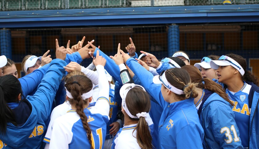 UCLA softball players huddle in March.