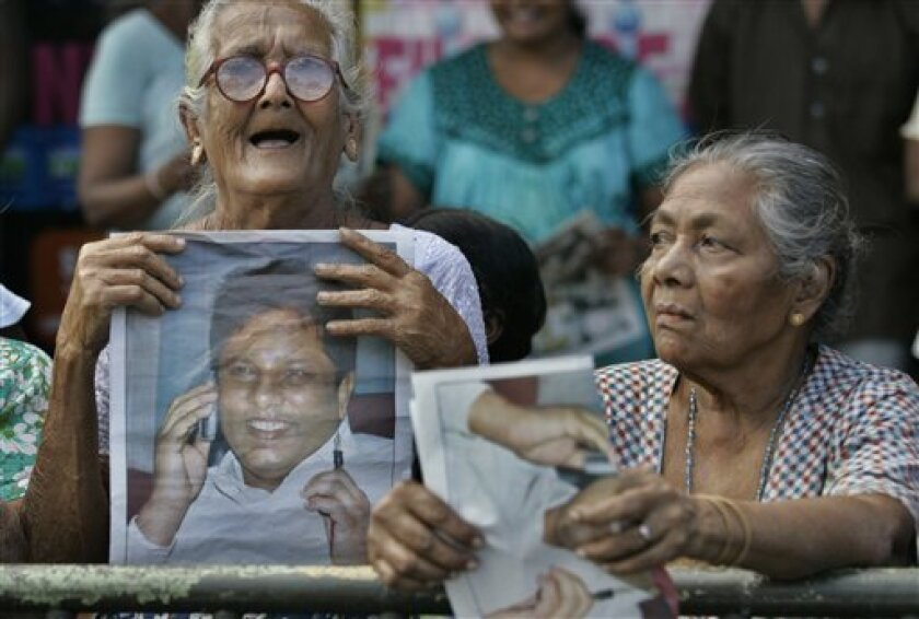 Elderly Sri Lankan women hold photograph of the Sunday Leader newspaper editor Lasantha Wickrematunge during his funeral procession in Colombo, Sri Lanka, Monday, Jan. 12, 2009. The funeral procession for a slain Sri Lankan journalist turned into a large anti-government protest Monday, with thousan