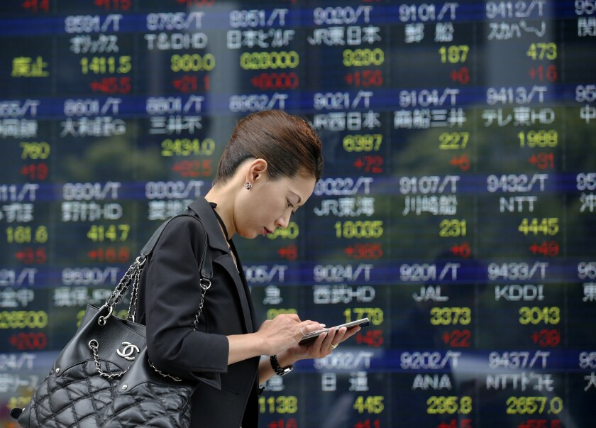 A woman uses a mobile phone in front of an electronic stock indicator of a securities firm in Tokyo, Monday, June 20, 2016. Most Asian stock markets jumped Monday as polls suggest British voters will choose to remain in the European Union in a referendum this week.