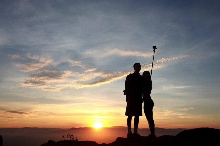 A couple use a selfie stick to capture the sunrise at the frequently mispronounced Cowles Mountain.