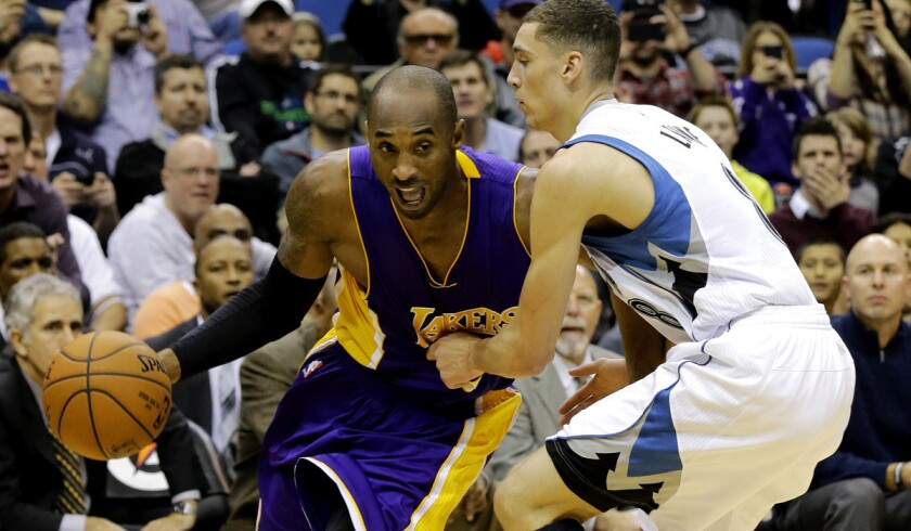 Lakers guard Kobe Bryant drives the baseline against Timberwolves guard Zach LaVine in the first half.