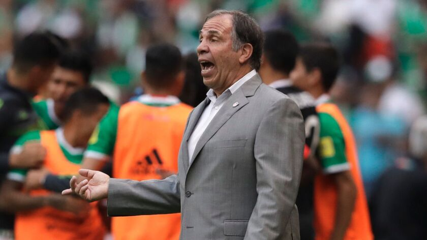 United States coach Bruce Arena gives instructions to his players as Mexico's Carlos Vela, 11, celeb