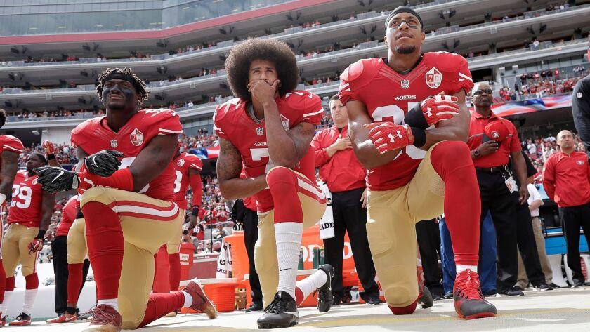 San Francisco 49ers quarterback Colin Kaepernick, center, and teammates kneel during the national anthem in Santa Clara, Calif. on Oct. 2, 2016.