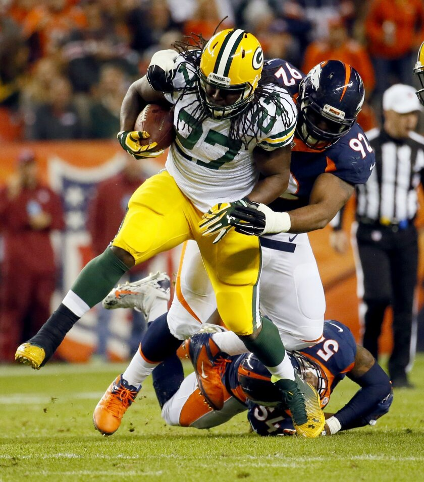 Green Bay Packers running back Eddie Lacy (27) is hit by Denver Broncos inside linebacker Brandon Marshall (54) and nose tackle Sylvester Williams (92) during the second half of an NFL football game, Sunday, Nov. 1, 2015, in Denver. (AP Photo/Jack Dempsey)