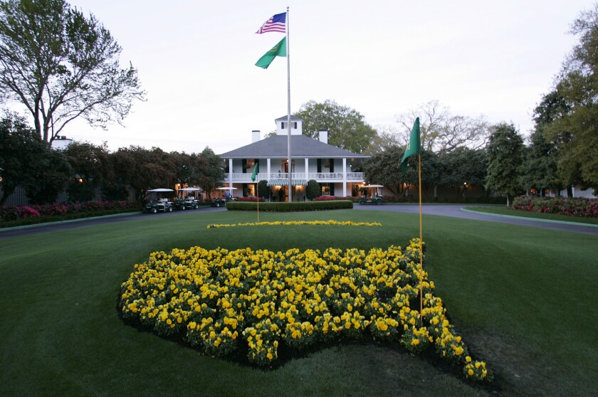 This file photo shows bright yellow flowers in the shape of the United States adorn the lawn at the clubhouse of Augusta National Golf Club.