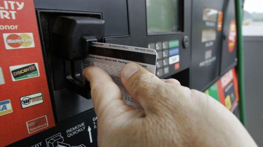 A customer swipes his credit card at a gas station pump in Morganton, N.C., Friday, June 15, 2007. A