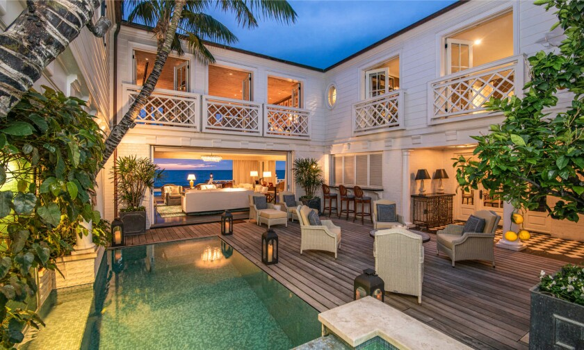 The two-story home enjoys ocean views from multiple balconies and an entertainer's deck that sits above the sand.