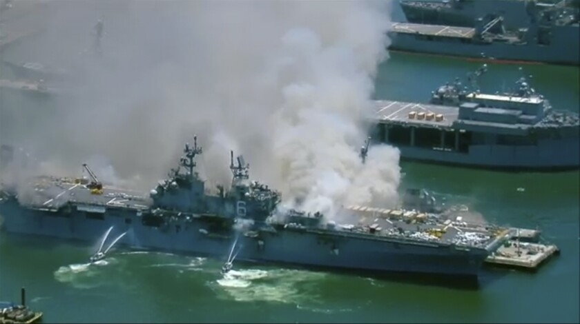Firefighting boats spray water onto the Navy assault ship Bonhomme Richard as smoke billows from the ship
