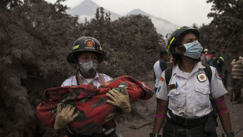 A firefighter carries the body of a child recovered near the Volcan de Fuego, which means in Spanish