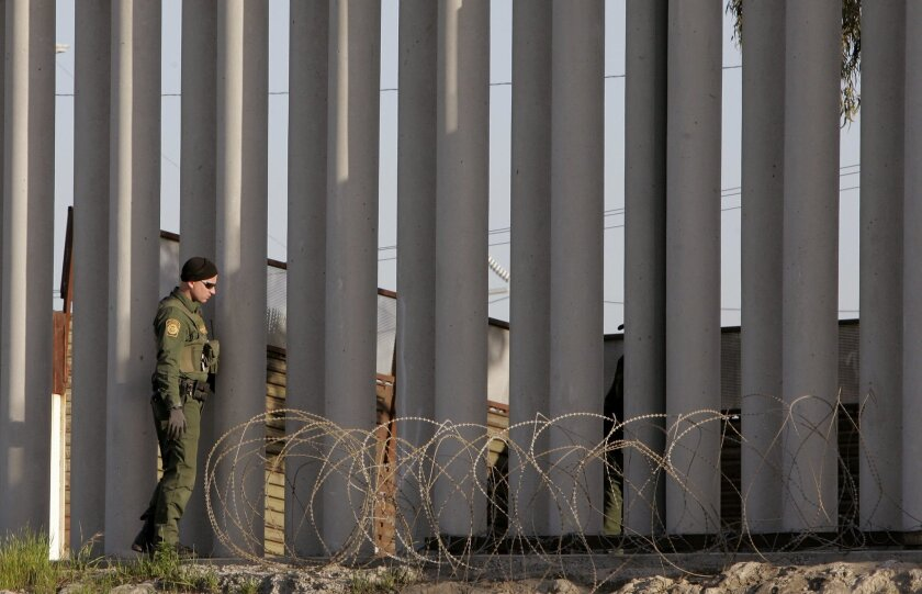 About a mile west of the San Ysidro border crossing a Border Patrol Agent looks for more people that may be in this area along this section of Bollard fence (steel reinforced concrete columns) where an illegal immigrant was just apprehended.
