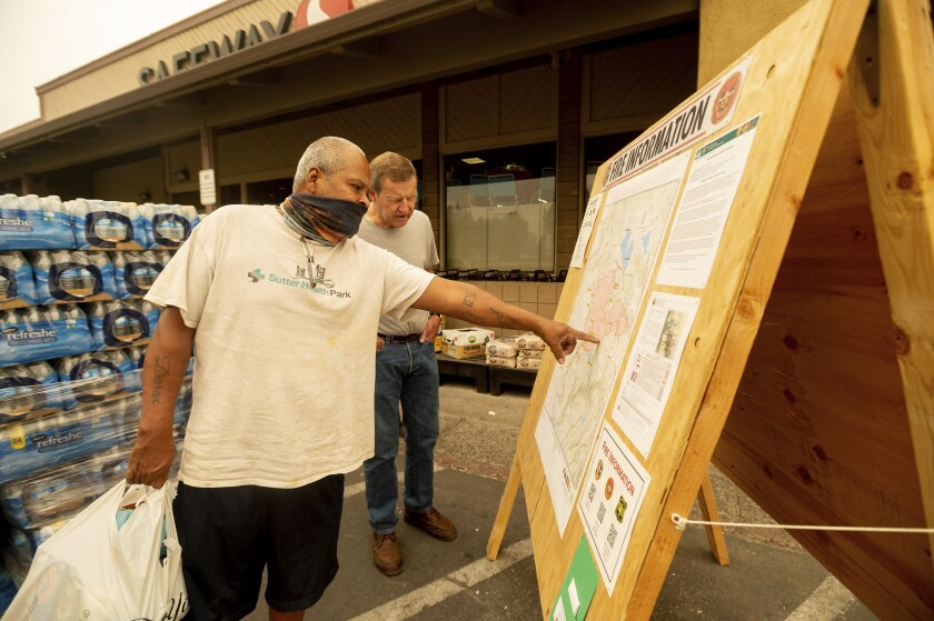 As evacuation orders take effect for the Dixie fire, Carlos Duran, left, and Rich McFeely examine a fire map in Quincy.