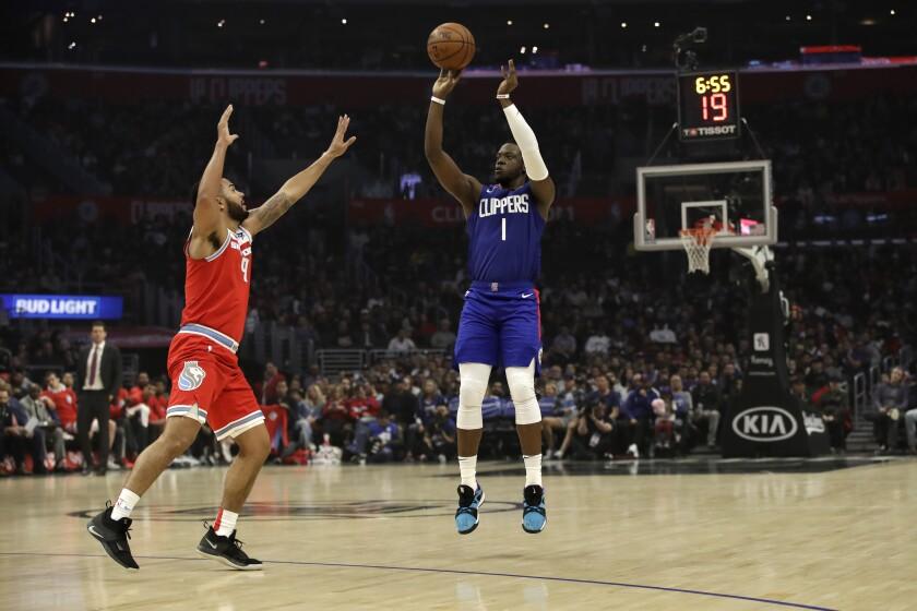 Clippers' Reggie Jackson, right, shoots over the Sacramento Kings' Cory Joseph.