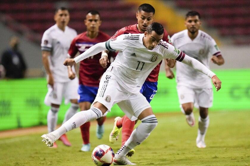 El mexicano Rogelio Funes Mori, al frente, y el costarricense Ronald Matarrita pelean por el balón