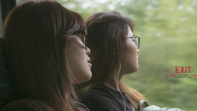 """Stella Zhu, left, and fellow student Julia Zhu on the school bus in the documentary """"Maineland."""""""