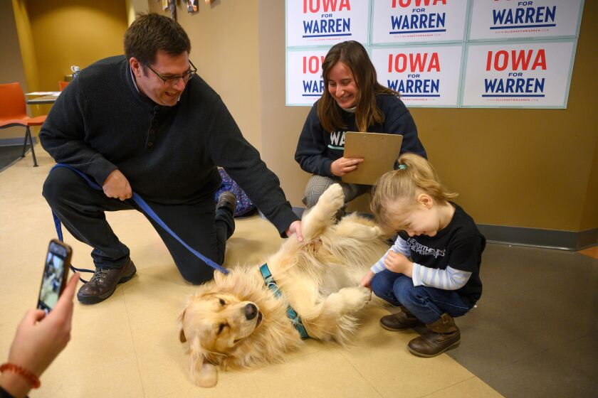 Elizabeth Warren's golden retriever Bailey gets to know a mother and daughter, with help from Alex Warren, at Wartburg College in Waverly, Iowa.