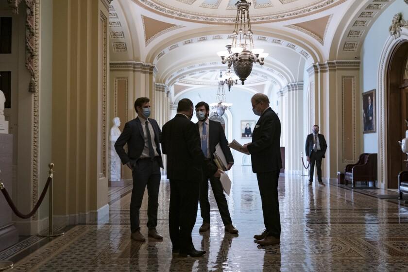 Congressional staffers wait in the ornate corridor outside the Senate chamber