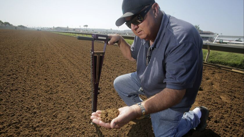 Holding a device that measures the moisture in the soil, director of track maintenance at the Del Mar Thoroughbred Club, Dennis Moore, inspects some of the dirt on the track.