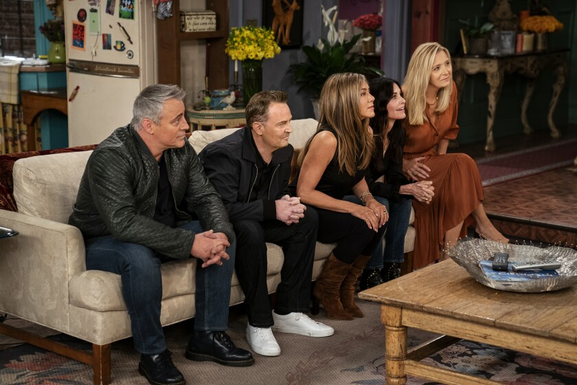 """The cast of """"Friends"""" on a couch in the series' apartment set, playing a game."""