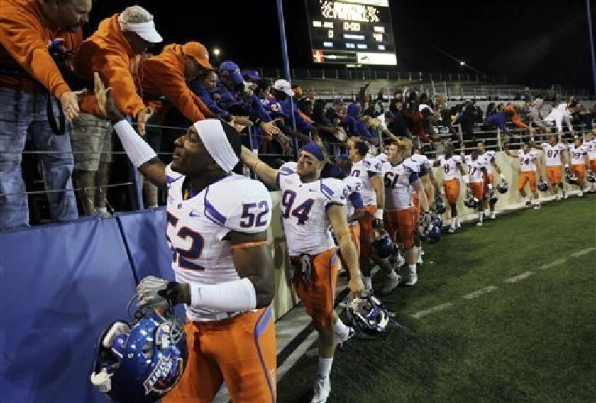 FILE - In this Oct. 16, 2010, file photo, Boise State players celebrate their 48-0 win over San Jose State after an NCAA college football game in San Jose, Calif. According to the BCS computers ratings, 21-20 is no different from 45-0. it's another part of the postseason system that is stacked against Boise State, TCU or Utah playing in the BCS national championship game this year. BCS officials say they don't want to encourage coaches to pile up points when games are already decided to boost their team's ratings.(AP Photo/Marcio Jose Sanchez, File)