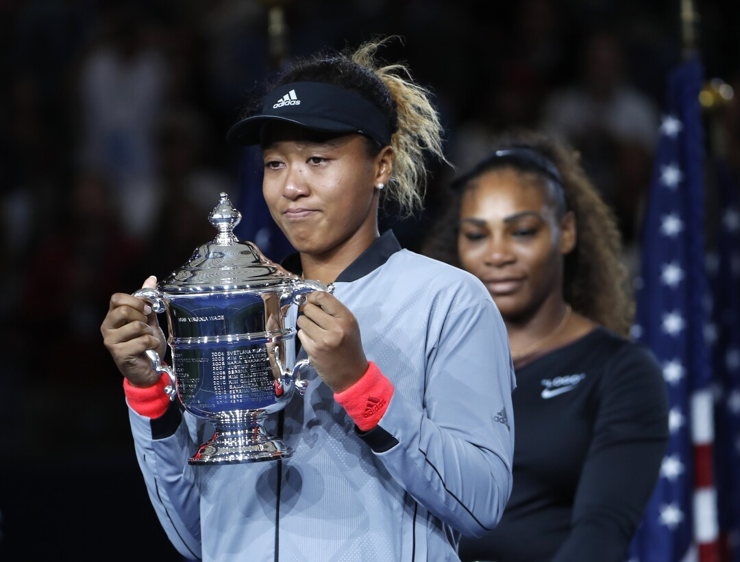 Naomi Osaka holds a large silver trophy with both hands, Serena Williams behind her.