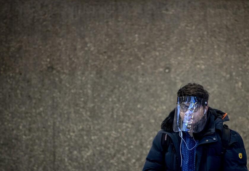 Un estudiante, con pantalla facial para protegerse del coronavirus, espera al metro en Fráncfort, Alemania, el 25 de noviembre de 2020. (AP Foto/Michael Probst)